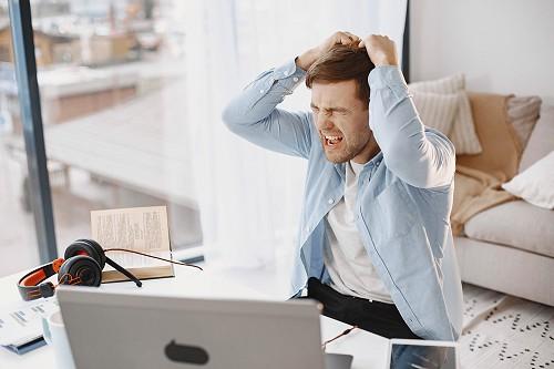 Frusztrált férfi a haját tépi a laptopja előtt.
