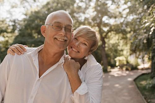 Boldog nyugdíjasok mosolyognak a kamerába.