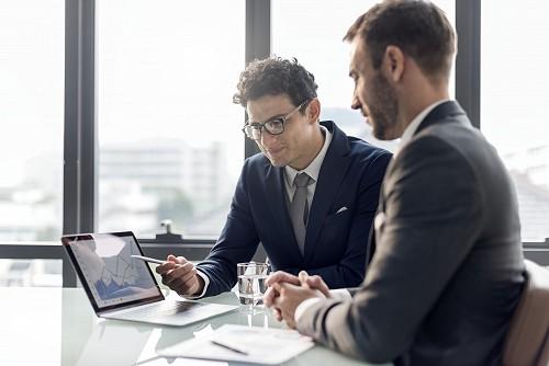 Egy vállalkozó prezentál laptopjára mutatva egy másik vállalkozónak.
