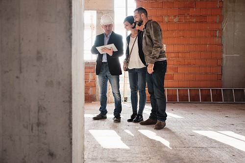 Fiatal pár építésszel ellenőrzik az építkezést adóvisszatérítés miatt.