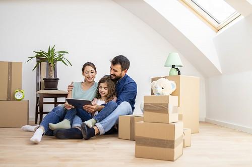 Fiatal pár kislányukkal boldogan ülnek a dobozok közt új otthonukban.