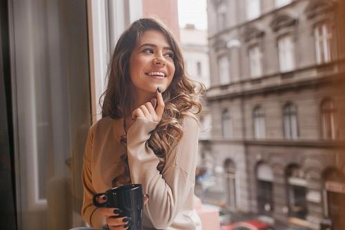 Ablaknál fiatal nő boldogan mosolyog, mert sikeresen rendezte hitelét.