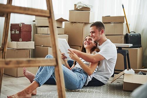 Fiatal pár dobozok közt lakáshitelének feltételeit olvassa mosolyogva.