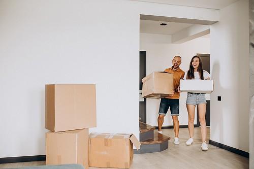 Fiatal pár új lakásába költözik éppen. Körülöttük dobozok.